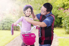 Dad fastens helmet on his daughter Stock Photography