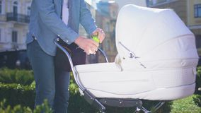Dad feeding baby in carriage with milk bottle, kid balanced nutrition, parenting. Stock footage stock footage