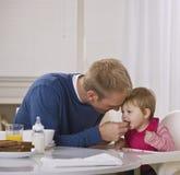 Dad Feeding Daughter Breakfast royalty free stock photos