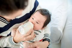 Dad feeding her baby daughter infant from bottle Adorable baby with a milk bottle. Baby milk eating bottle Royalty Free Stock Image