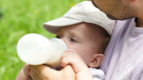 Dad feeding his baby from the bottle outdoor Royalty Free Stock Photo