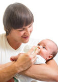 Dad feeding his baby infant from bottle Royalty Free Stock Images