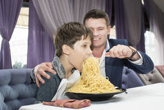 Dad feeding his son spaghetti. In a restaurant Royalty Free Stock Image