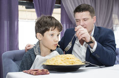 Dad feeding his son spaghetti. In a restaurant Stock Images