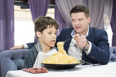 Dad feeding his son spaghetti. In a restaurant Royalty Free Stock Images
