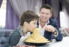 Dad feeding his son spaghetti. In a restaurant Royalty Free Stock Photos