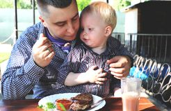 Dad feeds the child in a cafe royalty free stock image