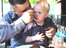 Dad feeds the child in a cafe stock photos