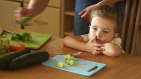Dad feeds her daughter. The little girl does not want to eat broccoli. She gets angry and turns away.