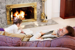 Dad fell asleep. Little girl reads by the fire while Dad naps Stock Images