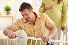 Dad fixing baby's bed Royalty Free Stock Photo