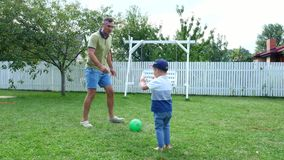 Dad with a four-year-old son playing ball, football, in the yard on a green lawn, in the summer.