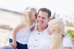 Dad Getting Kisses from His Cute Daughters Stock Photo