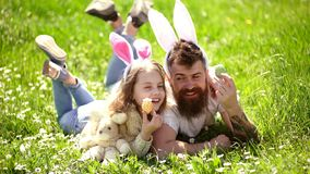Dad and girl found easter eggs in traditional hunting game in. Man with beard and cute child lay on grass with easter