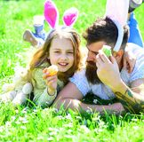 Dad and girl play easter egg hunt in spring garden. Man with beard and cute child lay on grass with easter egg in hand. Family feast concept. Father and child stock images
