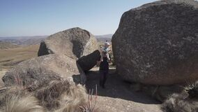 Dad gives his son a piggyback ride between huge rocks in the beautiful nature of Eswatini