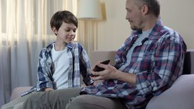 Dad giving cash from wallet to son for new toys, child pocket money, finances. Stock footage stock footage