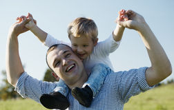Dad giving his young son a piggy back ride Stock Photo