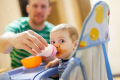 Dad giving infant formula for baby in highchair stock images