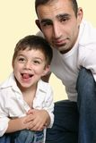 Dad with happy son. Portrait of young father with happy son, studio background Royalty Free Stock Photos