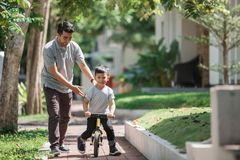 Kids ride bicycle push by his father Royalty Free Stock Photos