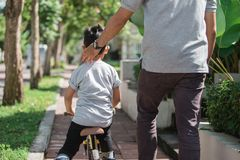 Kids ride bicycle push by his father Royalty Free Stock Images