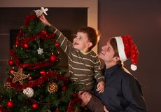 Dad helping boy to decorate christmas tree. Dad helping son to decorate christmas tree, boy putting up the top ornament, smiling royalty free stock photography