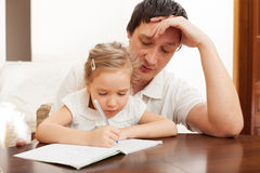 Dad helping daughter doing homework Stock Photography