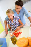 Dad helping daughter with meal preparation Stock Images