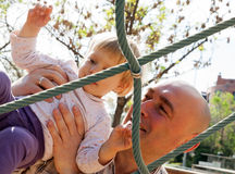 Dad helping his little daughter to climb ladder royalty free stock photo
