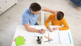 Dad helping his son with homework in room royalty free stock photo