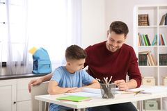 Dad helping his son with homework stock image