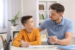 Dad helping his son with homework royalty free stock photography