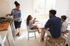 Dad helping kids with homework and mum cooks, elevated view Royalty Free Stock Images