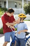 Dad helping son with helmet Stock Image