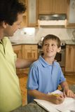 Dad helping son with homework. Caucasian mid-adult father helping pre-teen son with homework in kitchen royalty free stock photo