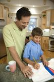 Dad helping son with homework. Caucasian mid-adult father helping pre-teen son with homework in kitchen royalty free stock photography
