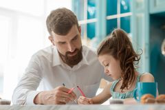 Dad helps daughter to draw. A picture for a school project. Having a good time with kids, creative activity and parenthood royalty free stock photo