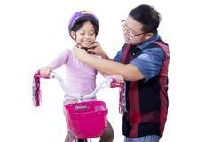 Dad helps his child to fasten helmet Stock Images