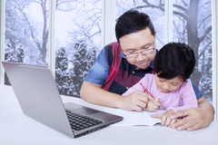 Dad helps his daughter doing school assignment Stock Image