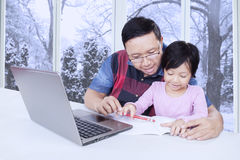 Dad helps his daughter studying at home with laptop Royalty Free Stock Photos