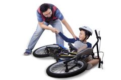 Dad helps his son after falling from bike Royalty Free Stock Photos