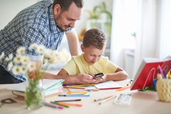 Dad helps his son to do homework. home schooling, home lessons. outside school classes with parents. father examines with his son stock photos