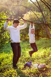 Dad helps support the boy hanging on the branch of a tree,  suns Stock Image