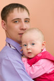 Dad and his baby. European young man and his baby daughter in his arms look into camera Stock Image