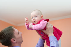 Dad and his baby. European young man holds his baby daughter above himself Royalty Free Stock Photos