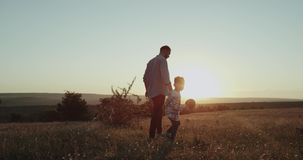 Dad with his boy three years old, at sunset in the middle of field playing with a small racquet for tennis table stock footage