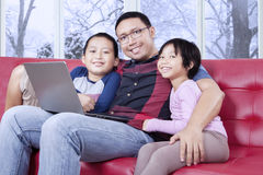 Dad and his children with laptop smiling at the camera Royalty Free Stock Image