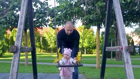 Dad and his cute infant daughter stands near swing with yellow autumn leaves then mom comes and brings beautiful yellowed leaf. Young dad and his cute infant stock video footage