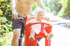 Dad with his daughter on a bike royalty free stock photo